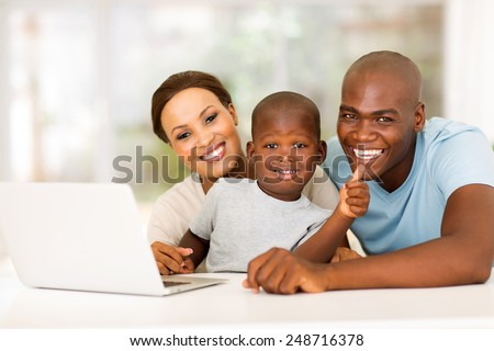 cute little african boy giving thumb up with parents at home - stock photo