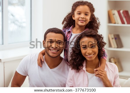 Cute little Afro-American girl and her beautiful young parents hugging, looking at camera and smiling while sitting on a sofa in the room. - stock photo
