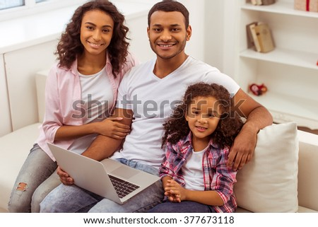 Cute little Afro-American girl and her beautiful young parents using a laptop, looking at camera and smiling while sitting on a sofa at home. - stock photo