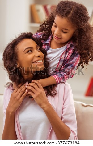 Cute little Afro-American girl hugging her beautiful young mother. Both looking at each other and smiling. - stock photo