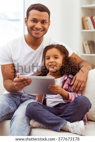 Cute little Afro-American girl in casual clothes and her handsome father using a tablet, looking at camera and smiling while sitting on a sofa in the room. - stock photo