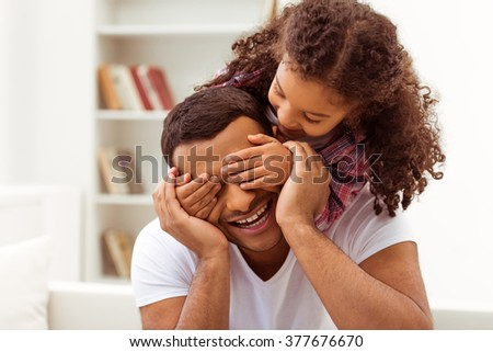 Cute little Afro-American girl in casual clothes covering her father eyes. Both smiling. - stock photo