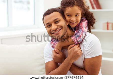 Cute little Afro-American girl in casual clothes cuddling her handsome father. Both looking at camera and smiling. - stock photo