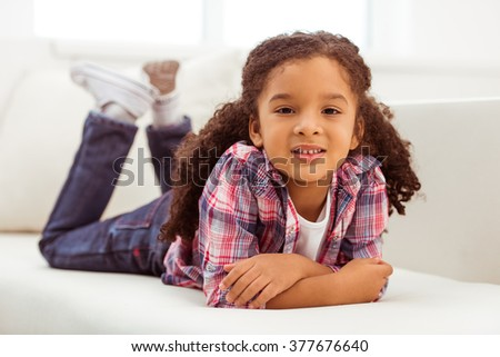 Cute little Afro-American girl in casual clothes looking at camera and smiling while lying on a sofa in the room. - stock photo