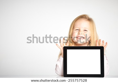 Cute little and smiling girl plays with a tablet - stock photo