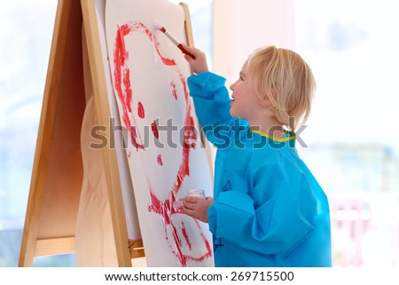 Cute little artistic child, blonde toddler girl, playing indoors painting and drawing on paper with brushes in bright sunny room with big windows at home or kindergarten - stock photo