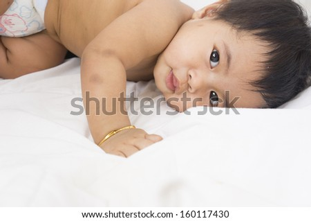 Cute little Asian baby girl lying in the bed