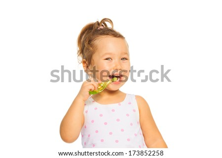 Cute little Asian girl cleaning teeth with toothpaste standing isolated on white - stock photo