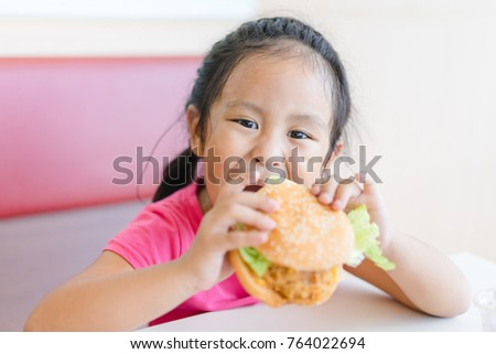 Cute little asian girl eating a burger in the restaurant