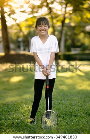 Cute little asian girl holding a badminton racket