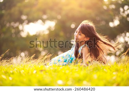 Cute little asian girl laying in the grass on a sunny summer day, Outdoor portrait - stock photo