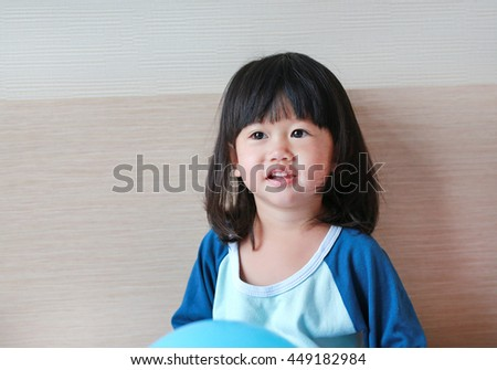 Cute little asian girl playing on bed with balloon. - stock photo