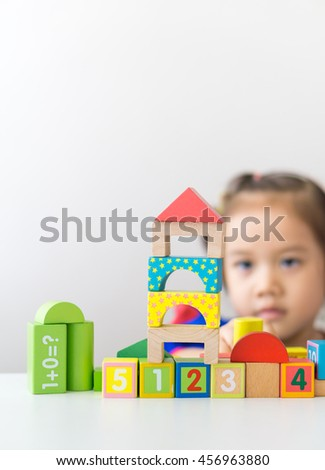 Cute little asian girl playing wooden building blocks.