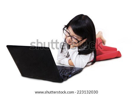 Cute little asian girl using laptop computer while lying in the studio - stock photo