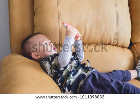 Cute little Asian 18 months / 1 year old baby boy child sitting on sofa watching a video from smart phone. Kids playing with smartphone. leisure & children & technology & internet addiction concept