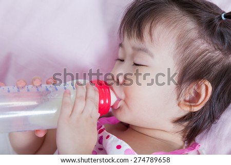 Cute little asian (thai) girl sleeping and sucking up milk bottle in bed.  - stock photo