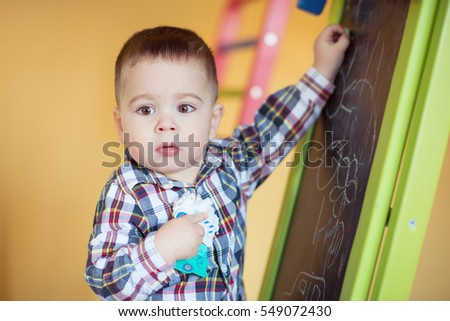 Cute little baby boy drawing with colorful chalk at the board