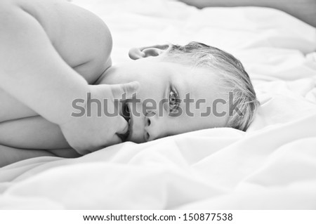 Cute little baby boy lying in the bed - stock photo