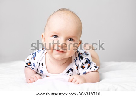 Cute little baby boy lying on bed and looking into camera. - stock photo
