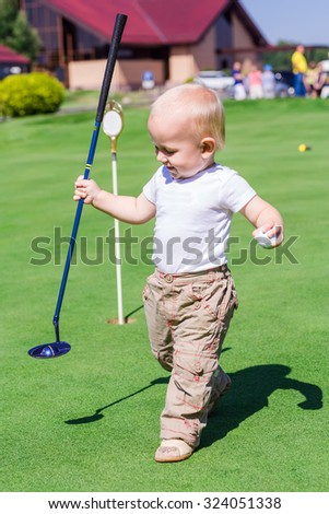 Cute little baby boy playing golf on a field outdoor