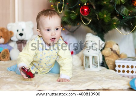 Cute little baby boy surprised portrait on blurred Christmas background with gifts and Christmas tree