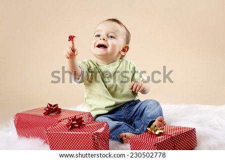 Cute little baby boy unwrapping christmas presents - stock photo
