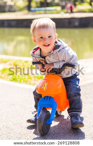 Cute little baby boy walk on the bike