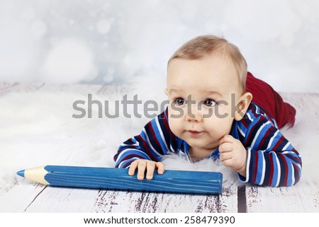 Cute little baby boy with big crayon - stock photo