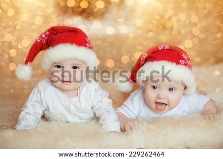 Cute little baby boys in Santa hat - stock photo