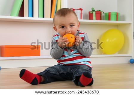 Cute little baby child eating orange fruit - stock photo