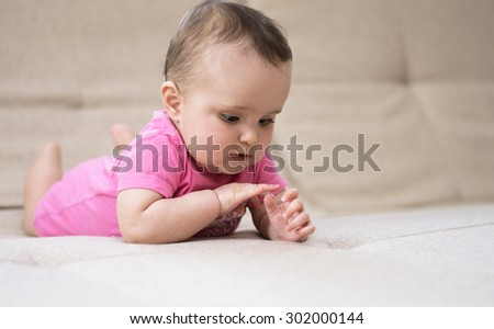 cute little baby girl admiring her manicure - stock photo