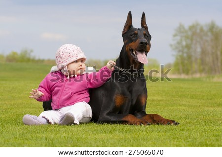 cute little baby girl and big black Doberman are sitting together on the grass - stock photo