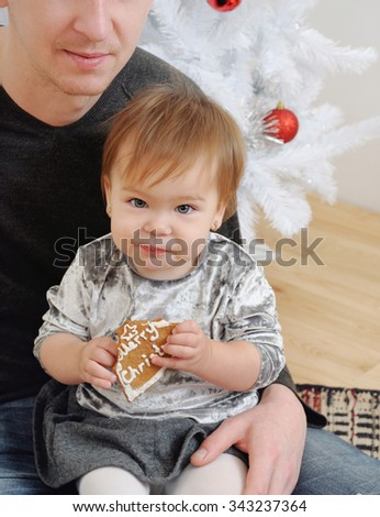 cute little baby girl eating cookies on father's knees near Christmas tree, happy holiday concept, happy family - stock photo