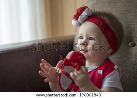 Cute little baby girl holding shoe  - stock photo