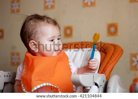 Cute little baby girl in the bib sitting in the high chair and  ready to her first food, indoor close-up portrait, health nutrition concept - stock photo