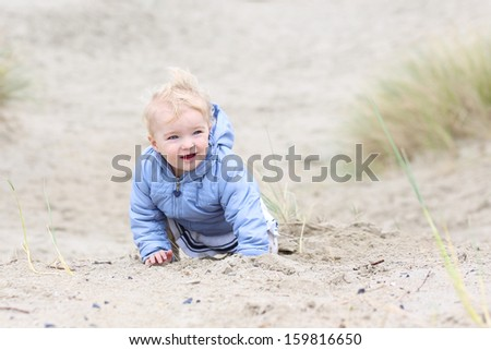 Cute little baby girl in warm coat plays with sand in the dunes
