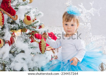Cute little baby girl is  decorating the christmas tree - stock photo