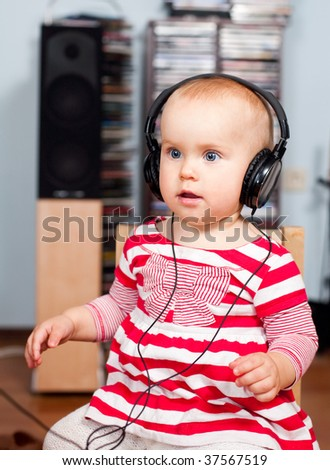 Cute little baby girl listening to a music