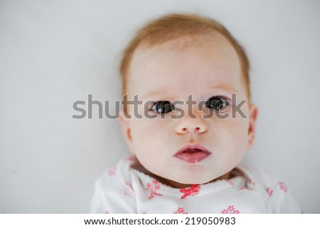 cute little baby girl looking at you. Primarily focus on eyes.