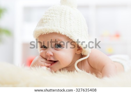 Cute little baby girl looking into the camera and weared in white hat.  - stock photo