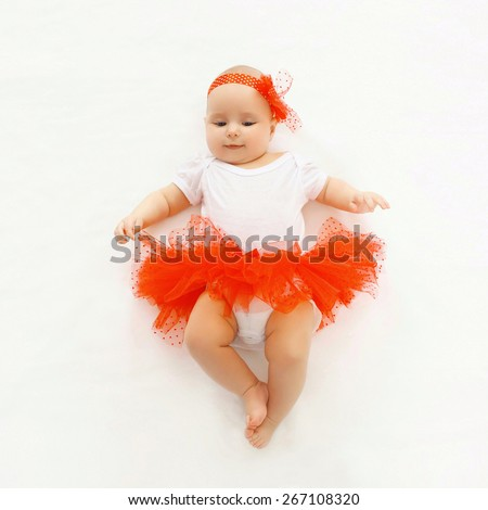 Cute little baby girl lying in the red skirt, top view - stock photo