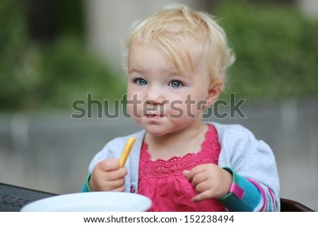 Cute little baby girl sitting on terrace at cafe eating delicious french fries