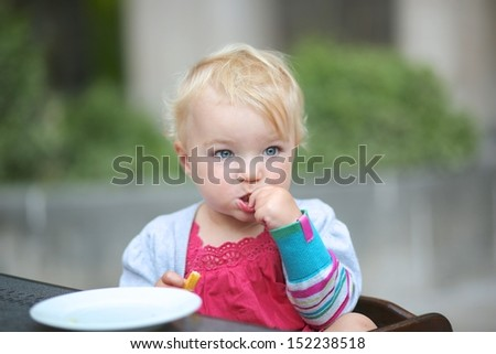 Cute little baby girl sitting on terrace at cafe eating tasty french fries - stock photo