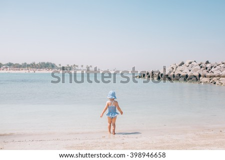 Cute little baby girl toddler standing near the water at the beach - stock photo