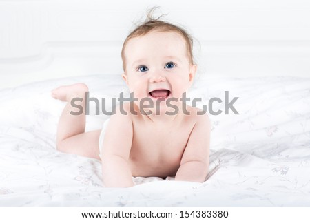 Cute little baby girl with beautiful big eyes playing on her tummy on a white blanket wearing a diaper - stock photo