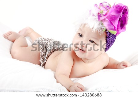 Cute little baby girl with big black eyes and flower in her hair