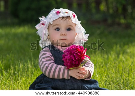 cute little baby girl with big blue eyes in a summer hat with flower in her hands. child sitting on a green grass on the nature in the park, outdoor - stock photo
