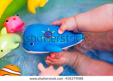 Cute little baby having fun in a small inflatable pool with many toys - stock photo