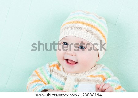 Cute little baby in a knitted jacket and hat on a green blanket - stock photo