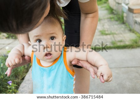 Cute little baby in summer park with mother on green grass. Sweet boy and mom outdoors. Serious face kid with mum on a learning walk. Portrait of a child